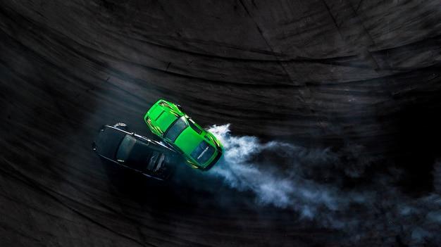 Drifting battle der draufsicht der luft zwei auf rennstrecke, zwei autos kämpfen drift, rennwagenansicht von oben.