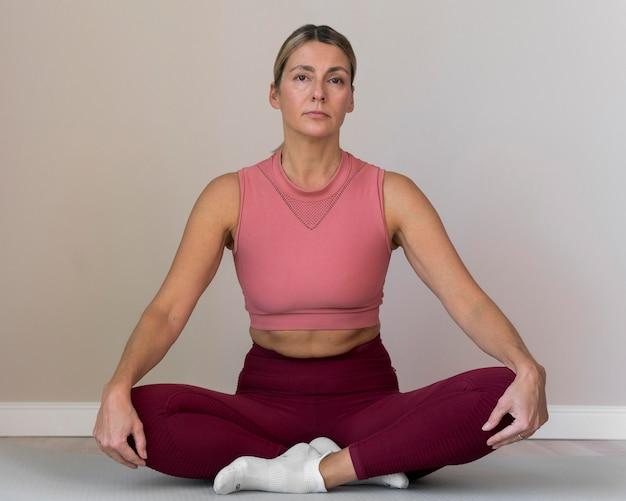 Drinnen reife frau, die yoga macht
