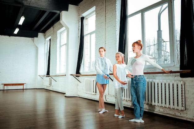 Dritte ballettstellung. die rothaarige gymnastiklehrerin und ihre schüler sehen konzentriert aus, während sie in der dritten ballettposition stehen