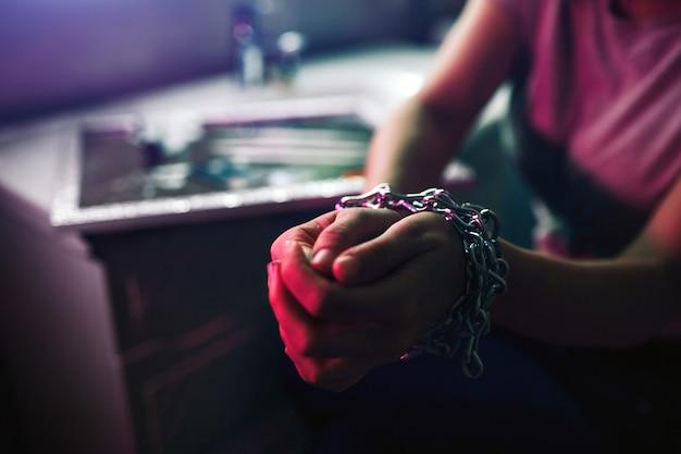 Drogen binden hände. wähle das leben, nicht drogen. nahaufnahme der frau band hände mit metallkette in der toilette des nachtclubs. besessenheit und schmerz.