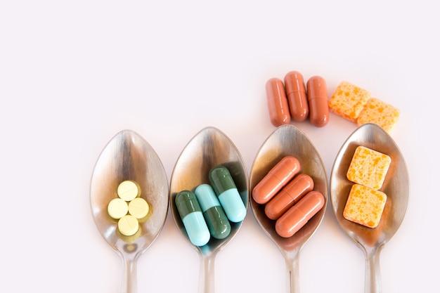 Drogen im löffel, bunt von den mundmedikationen auf weißem hintergrund