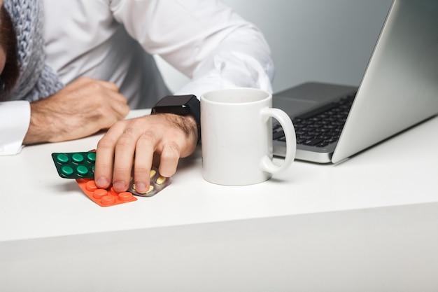 Drogen, medikamente am arbeitsplatz. der krankheitsmanager im weißen hemd sitzt im büro und döst an seinem arbeitsplatz in der nähe des laptops. indoor, studioaufnahme, isoliert, nahaufnahme