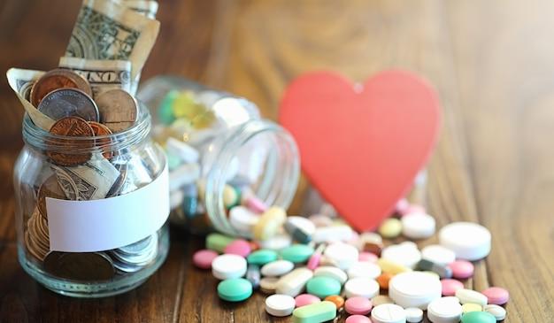 Drogen und münzen in einem glasgefäß auf einem holzboden. taschengeld aus münzen in einer bank für medizinische dienste. sparschwein in einem glasgefäß mit münzen.