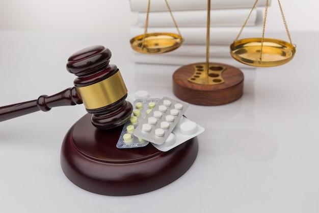Drogen und recht. richter hammer und bunte pillen auf einem holzschreibtisch