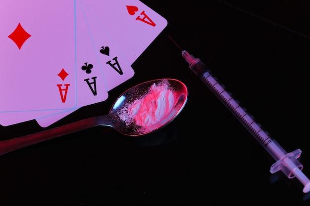 Drogen- und spielsucht. löffel mit drogenpulver, spritze und vier assen auf schwarzem hintergrund mit rot-blauem neonlicht