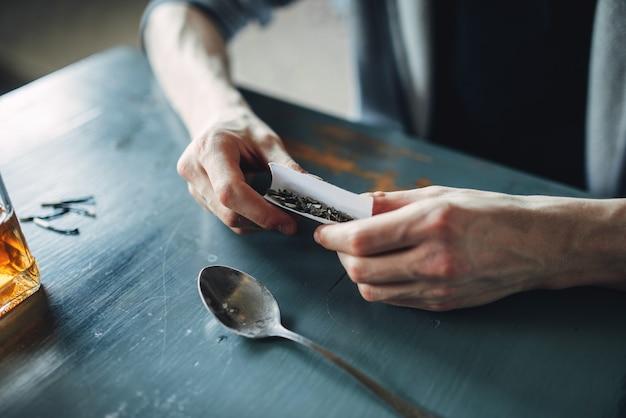 Drogenabhängige hände bereiten eine dosis vor, draufsicht