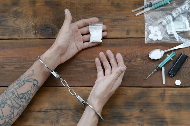 Drogenhändler wurden zusammen mit ihrem heroin festgenommen. die polizei verhaftet den drogendealer mit handschellen