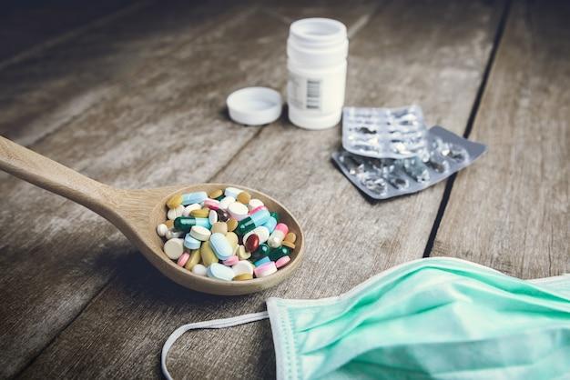 Drogenpille auf hölzernem löffel für ihre behandlung ihre gesundheit auf hölzernem hintergrund