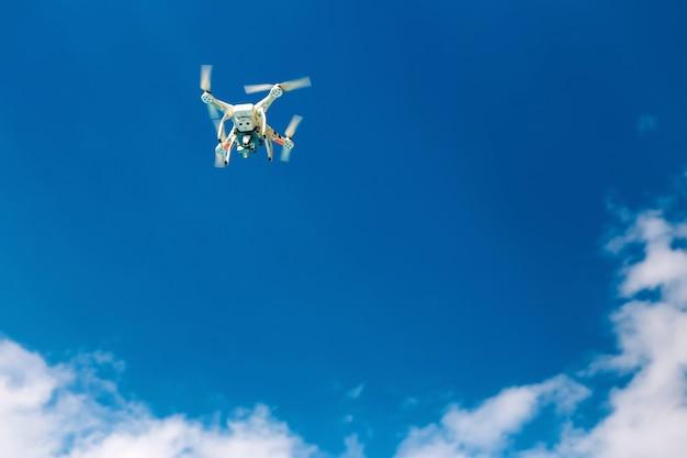 Drohne auf blauem himmel mit wolken. drohne schwebte am himmel.