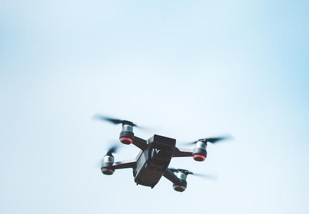 Drohne, die über blauen himmel fliegt