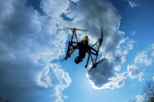 Drohne, die vorbei in einen hellen blauen himmel fliegt. neue technologie beim aero-fotoshooting.