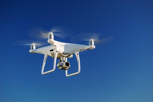 Drohne fliegt über den blauen himmelhintergrund