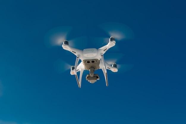 Drohne fliegt über feld bedeckt mit schnee an sonnigem wintertag