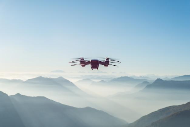 Drohne fliegt über neblige und schneebedeckte hohe hügel und berge