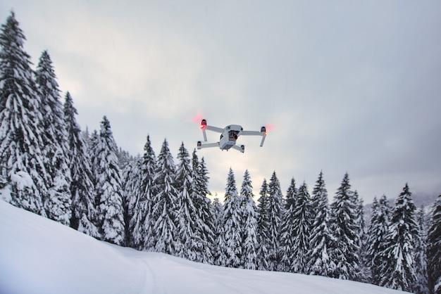 Drohne ist gerade im flug nach schneefall in der nähe von bäumen aufgestanden