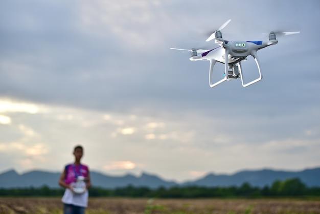 Drohne kontrolle durch fernbedienung und ein junge verschwommen fliegen vor wolkenregen