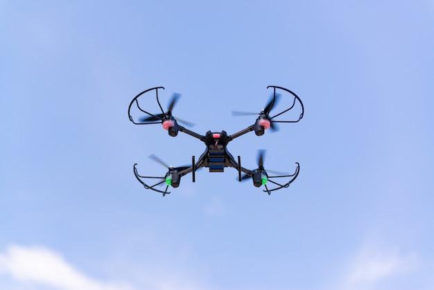 Drohne oder hubschrauber im blauen himmel fliegen.