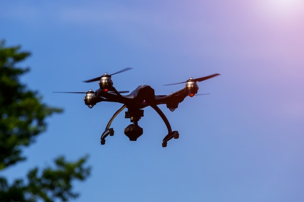 Drohne oder uav, die oben in blauen himmel fliegen