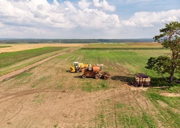 Drohne über ländlichen erntemaschinen steht auf weitfeld-luftaufnahme. landwirtschaftslandschaft.