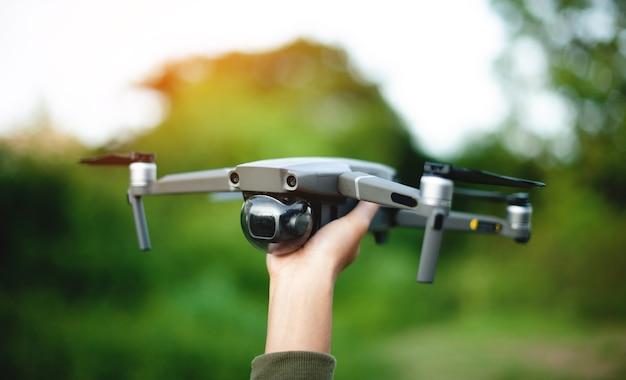 Drohne und meine hand machen sie sich bereit für einen vermessungsflug. und bereit für die fliegende high-angle-fotografie