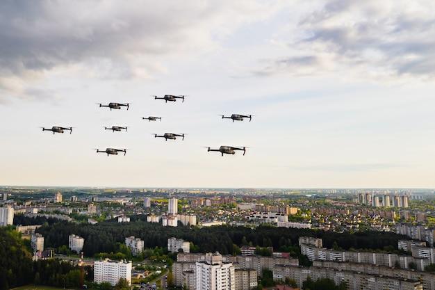 Drohnen fliegen über die häuser der stadt. stadtlandschaft mit drohnen, die darüber fliegen, quadrocopter, die über die stadt fliegen.