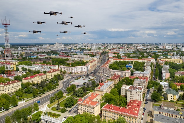 Drohnen fliegen über eine wohnstadt. stadtlandschaft mit drüber fliegenden drohnen, quadrocopter