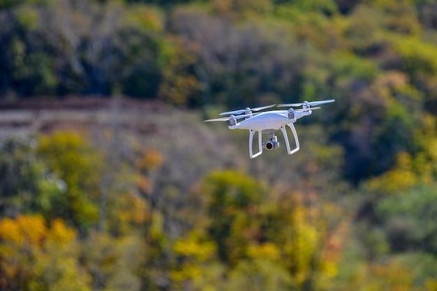 Drohnen-quadcopter mit hochauflösender digitalkamera, die im hinterhof eines waldes fliegt