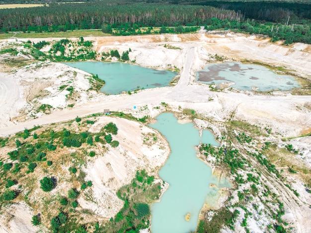 Drohnenansicht auf einem überfluteten kaolinsteinbruch mit türkisfarbenem wasser und weißem ufer