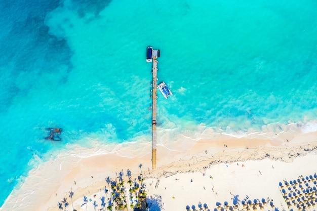 Drohnenansicht des tropischen strandes mit brücke, palmen und booten
