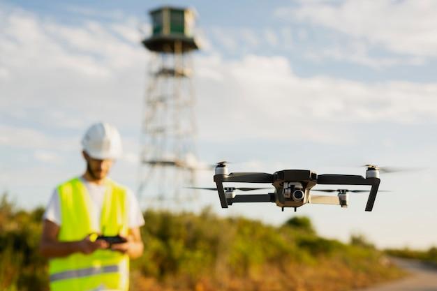 Drohnenbediener steuert eine drohne in einer ländlichen umgebung