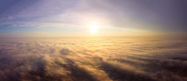 Drohnenflug über den nebel. orange morgensonne, strahlen beleuchten den dichten nebel