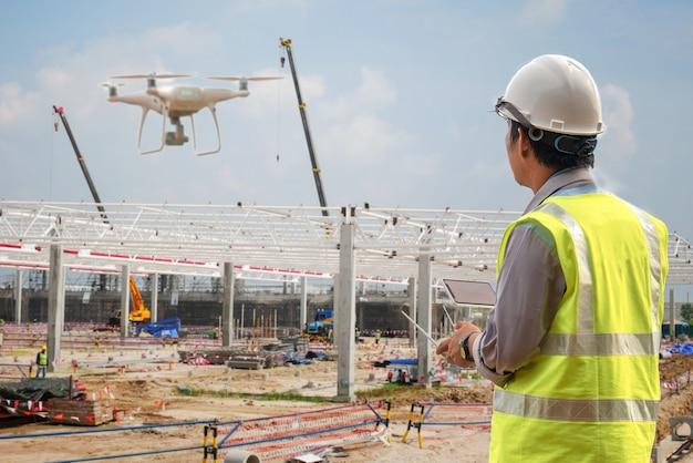 Drohneninspektion. betreiber, der baustellenkontrolle durch bauingenieur kontrolliert