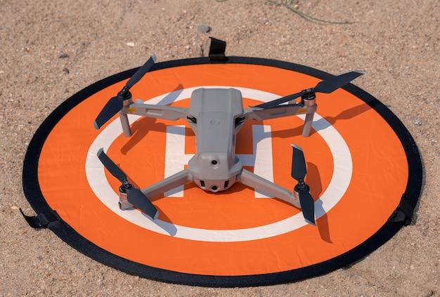 Drohnenlandung auf orangefarbenem landeplatz auf sandboden, um staub in kameralinse und kardanmotor zu schützen