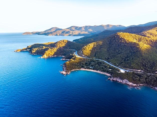 Drohnenpanorama des sonnenuntergangs in chalkidiki mit blauem meer und bergen, griechenland