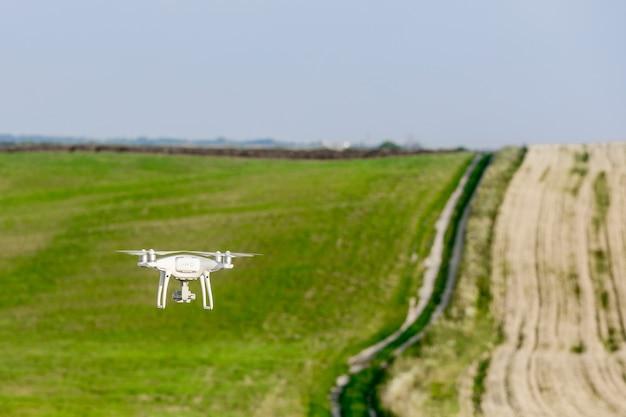 Drohnenquadcopter auf grünem maisfeld