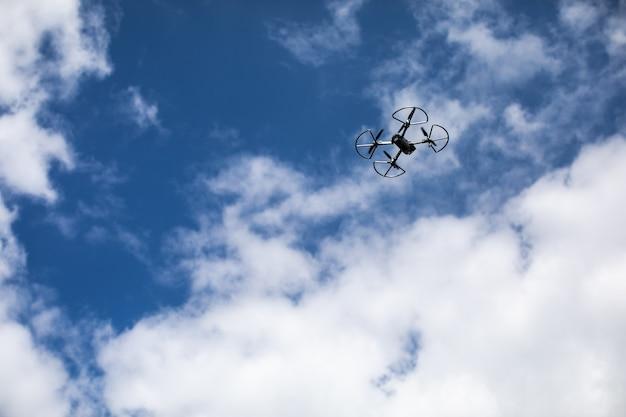 Drohnenquadcopter mit digitalkamera auf blauem himmel