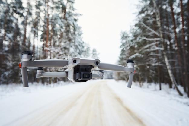 Drohnenquadcopter mit kamera, die im winterwald fliegt