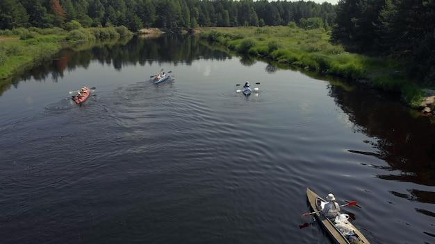 Drohnensicht auf gruppenleute, die auf dem wasser schwimmen. luftdrohnenansicht des gruppenkajaks im see. kajak- und kanufahren entlang der riverbed aerial view. rafting. ein boot verfolgen
