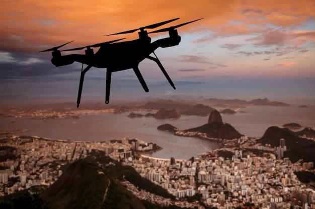 Drohnensilhouette, die über der stadt rio de janeiro fliegt.