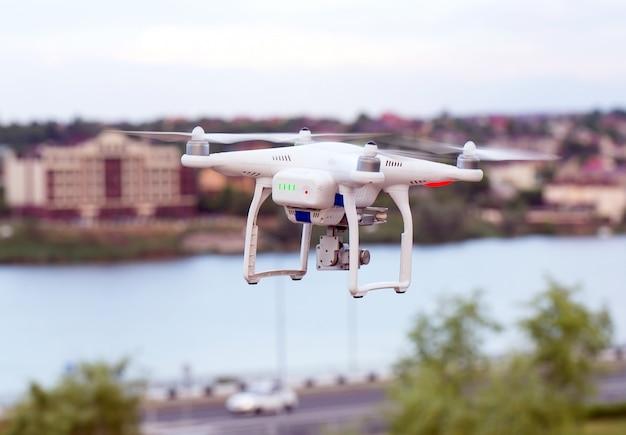 Drone quad copter mit hochauflösender digitalkamera fliegt über der stadt