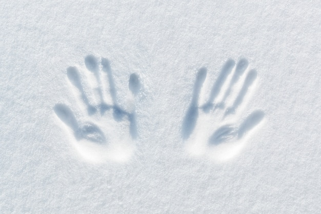 Druck von zwei händen auf dem schnee