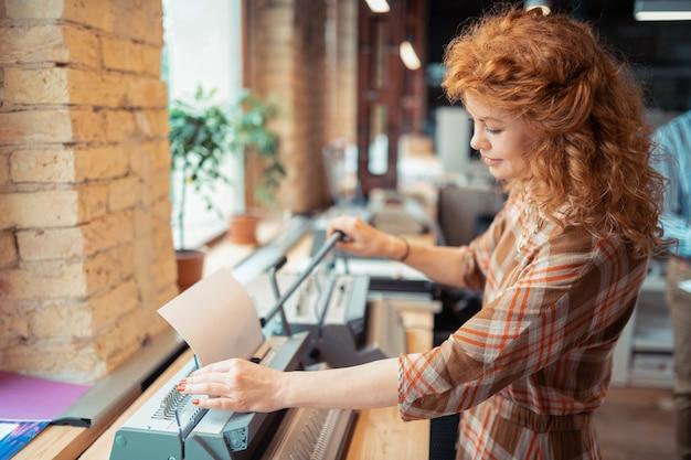 Drucken von dokumenten. lockige schöne rothaarige frau mit lockigem haar, die beim drucken von dokumenten lächelt