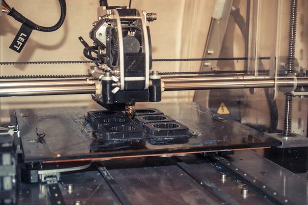 Drucker druckt graue objekte auf spiegelnde oberfläche in nahaufnahme