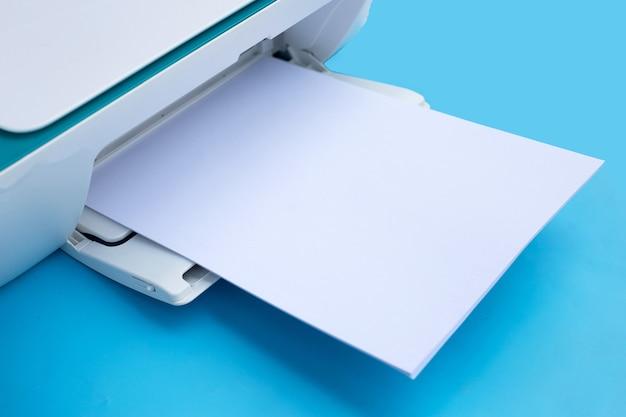 Drucker und papier auf blauem hintergrund.