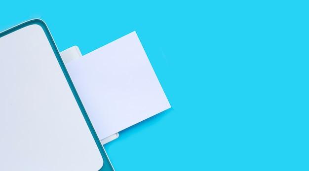 Drucker und papier auf blauer oberfläche