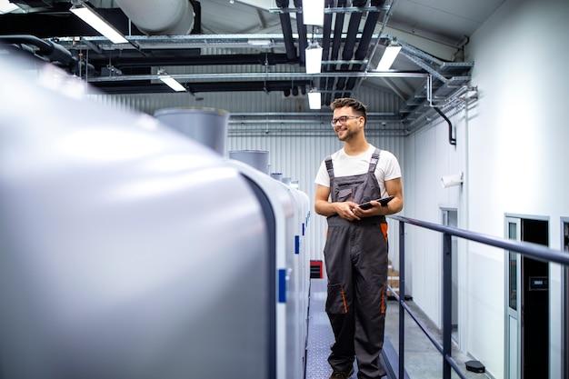 Druckereiinnenraum mit moderner offsetdruckmaschine und bediener, der die druckqualität überprüft quality
