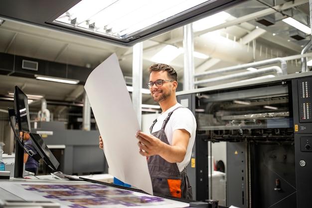 Druckereimitarbeiter, der die qualität des aufdrucks überprüft und den druckprozess kontrolliert.