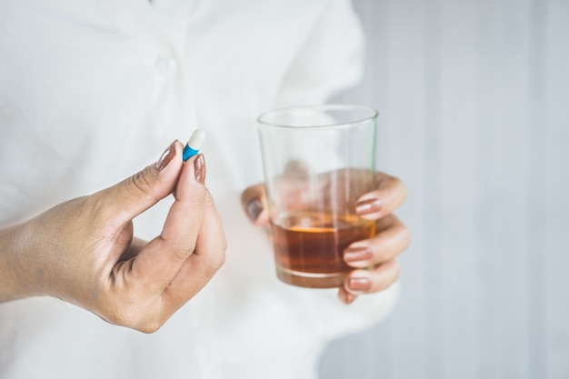 Druckfrau, die schlaftablette mit alkohol nimmt