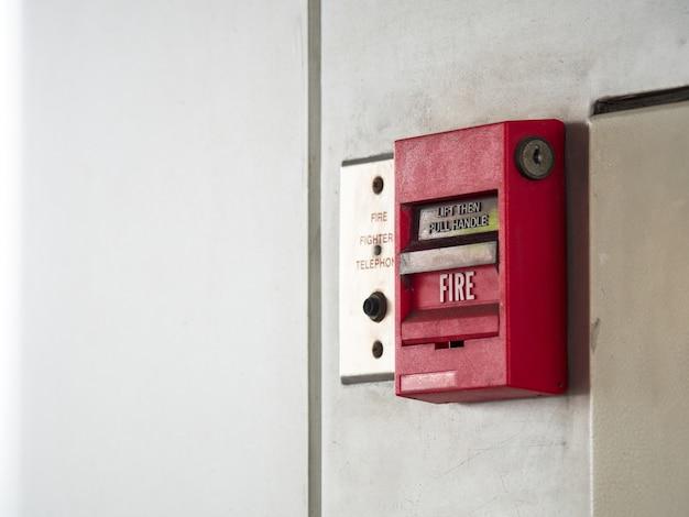 Druckknopfschalter feueralarm auf grauer wand für alarm- und sicherheitssystem mit feuer extinguer