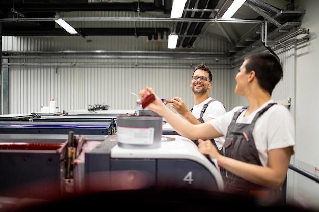 Druckmaschinenbediener, die gemeinsam mit farbe in der druckerei arbeiten.